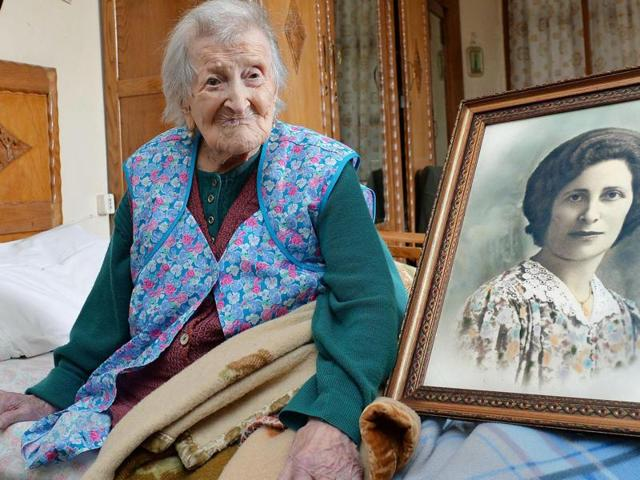 Emma Morano poses next to a picture depicting her where she was young, in Verbania, Italy, Friday, May 13, 2016. At 116 years of age, is now the oldest person in the world. Not only that, but she is believed to be the last surviving person in the world who was born in the 1800s, coming into the world on Nov. 29, 1899.