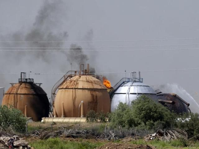 Iraqi firefighters try to extinguish a fire at a natural gas plant in Taji, 20km north of Baghdad. The Islamic State group launched a coordinated assault on Sunday on a natural gas plant north of the capital that killed more than a dozen people, according to Iraqi officials.