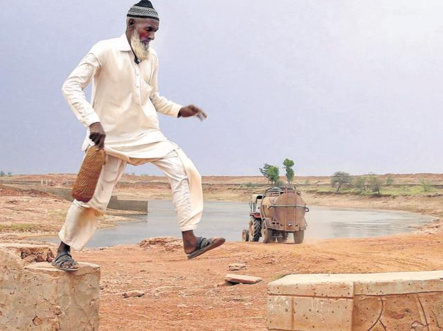 Caretaker Mohammed Akbar  takes a round of the pond as a tanker takes water at Kumhari village.