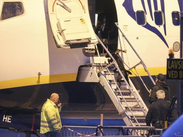 A police bomb officer stands in front of a Ryanair plane at Moss Airport Rygge, Norway.