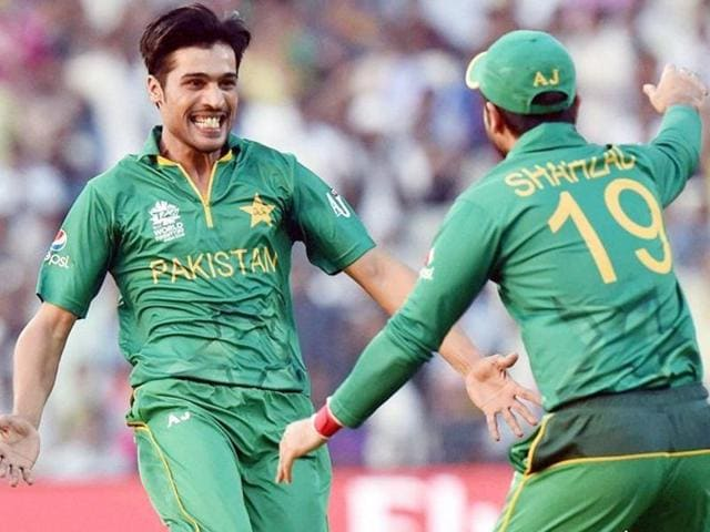 Pakistani bowler Mohammad Amir (L) celebrates with his team-mate Shahzad after taking a wicket.