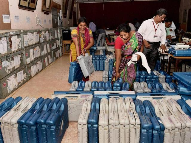 Polling officials check the Electronic Voting Machines (EVM) at a distribution centre in Chennai ahead of voting for Tamil Nadu assembly polls.