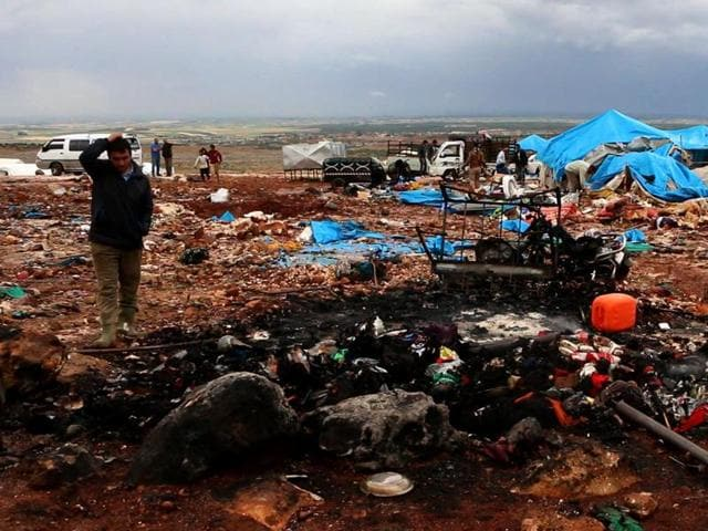 An image grab taken from AFPTV shows a Syrian man looking at the destruction at a camp for displaced people near the town of Sarmada in Syria's Idblib province, near the border with Turkey, following an air strike on May 5, 2016.