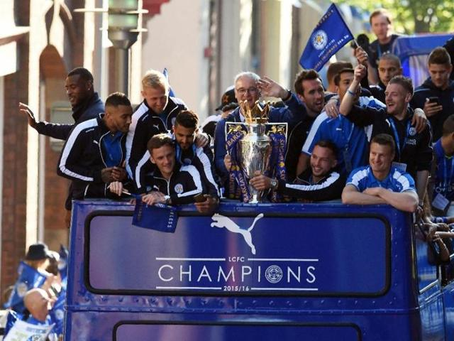 Leicester City's manager Claudio Ranieri (C) holds the Premier league trophy as the team take part in an open-top bus parade through Leicester.