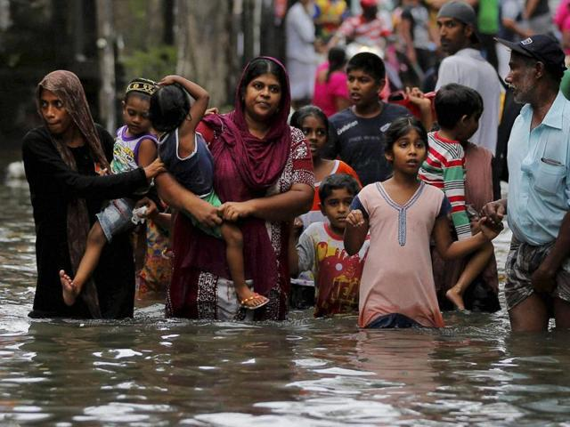 Residents wade through a road submerged in flood waters in Colombo.