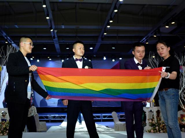 Hu Mingliang (second from left) and his partner Sun Wenlin (second from right) sign on a rainbow flag - a symbol of the LGBT movement - during their legally unrecognised wedding ceremony in Changsha, central China's Hunan province on May 17. Hu and Sun tied the knot in a wedding ceremony where imitation marriage certificates were presented despite a Chinese court ruling on April 13 against the two men seeking to marry.
