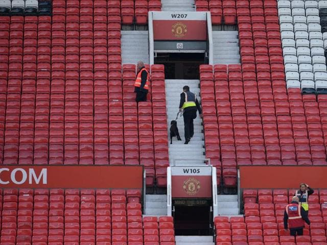 A sniffer dog searches the stands after fans evacuated Old Trafford stadium in Manchester, on May 15, 2016, after the Premier League match between Manchester United and Bournemouth was abandoned.