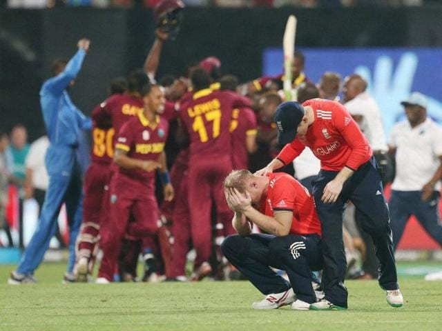 West Indies' Marlon Samuels (R) celebrates winning the World T20 final as England's Ben Stokes walks past.