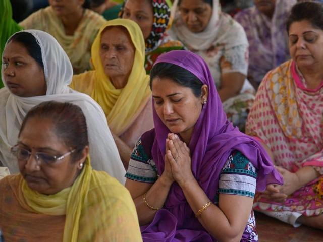 Followers of spiritual leader Nirankari Baba Hardev Singh mourn his death, at the Nirankari Satsang Bhawan centre in Amritsar.