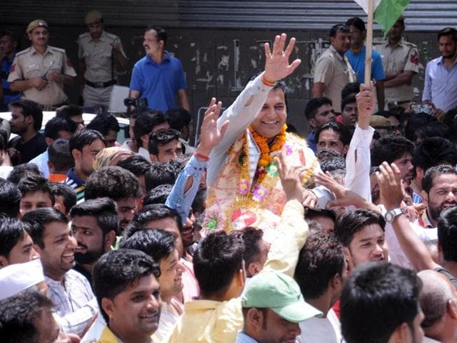 Congress' Anand Kumar celebrates victory at Khichripur in East Delhi on May 17, 2016.