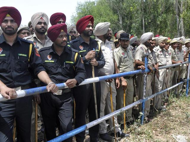 Police personnel take guard at a barricade put up to stop Aam Aadmi Party activists from entering Chandigarh for staging a protest outside Punjab chief minister Parkash Singh Badal's Chandigarh residence, in SAS Nagar on Monday.