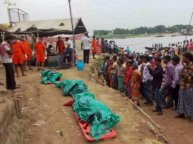 People gather near the bodies recovered in a search operation after a boat sank, in Kalna, Burdwan.