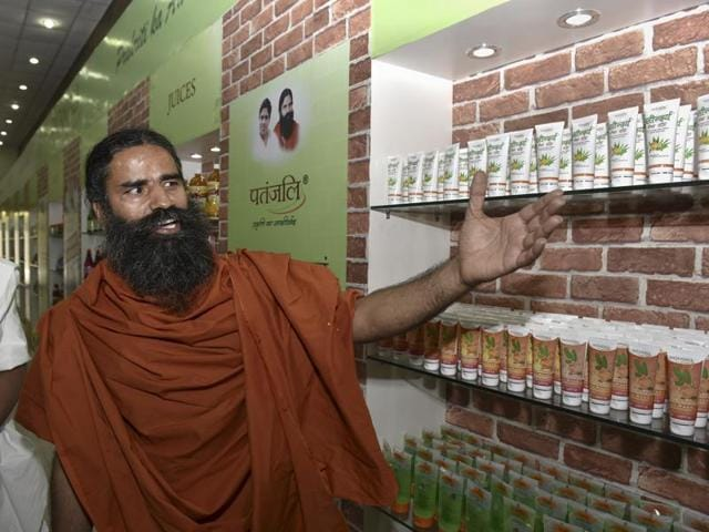 Ramdev shows Patanjali's products during press conference in New Delhi.