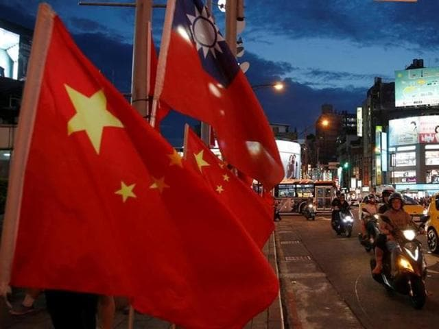 Flags of China and Taiwan flutter next to each other in Taipei, Taiwan