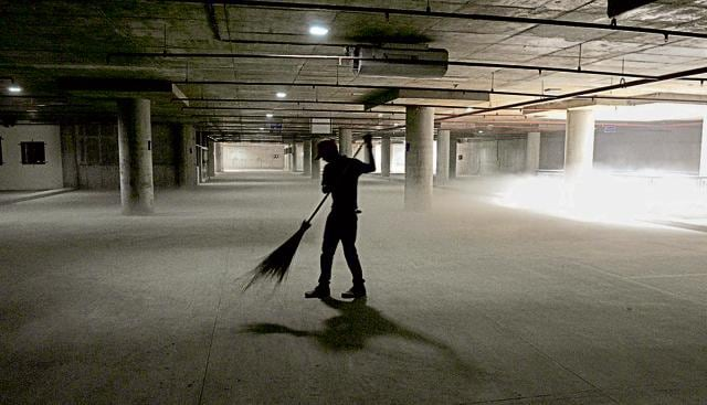 A worker cleaning the empty floor of multi-level parking in Sector 17 Chandigarh on Tuesday.