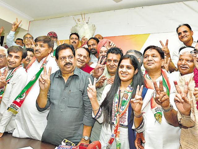 Delhi Congress president Ajay Maken (extreme right) strikes a victorious pose with his party's winners in the municipal bypoll on Tuesday.