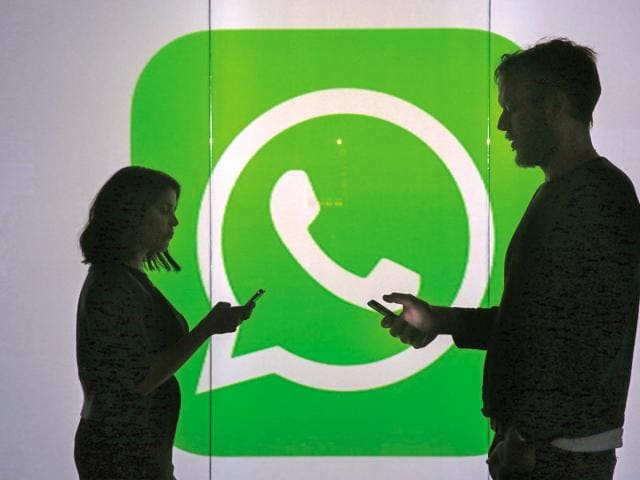 People are seen as silhouettes as they check mobile devices whilst standing against an illuminated wall bearing WhatsApp Inc's logo in this arranged photograph in London in January.