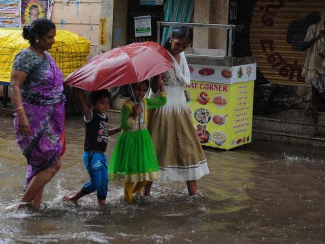 A  woman walks under an umbrella amid heavy rains at Patinapakkam in Chennai on May 17, 2016.