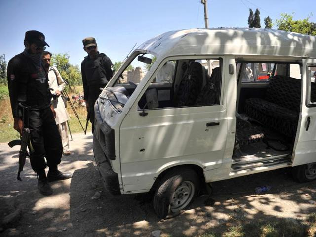Pakistani police officials inspect the site of a roadside bomb explosion in Peshawar.
