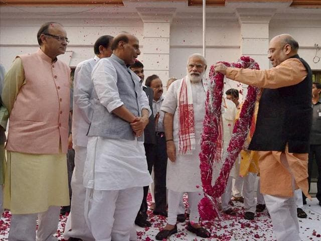 BJP president Amit Shah garlands Prime Minister Narendra Modi as Rajnath Singh and other leaders look on before a meeting at the party office in New Delhi on Thursday.
