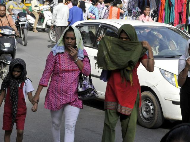 A mother covers her child with a handkerchief to protect him from the blazing sun in Indore.
