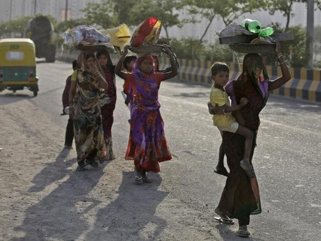 Construction workers carry empty plastic bottles used by them to store water, as they walk back to their huts on a hot afternoon in New Delhi.