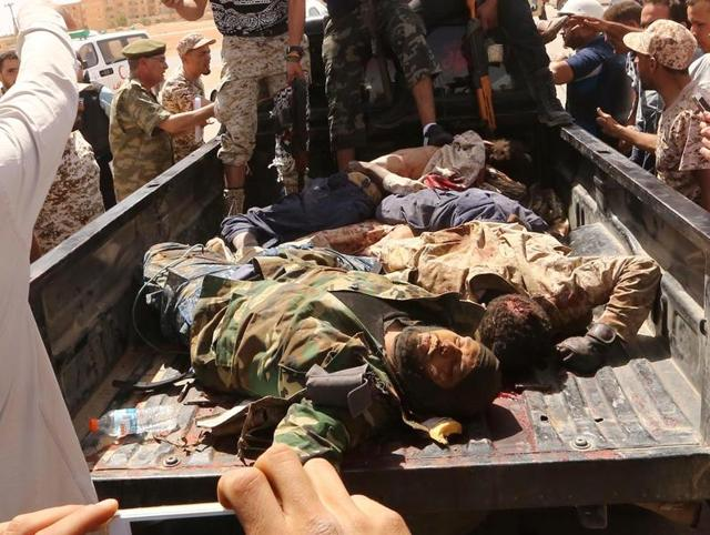 Libyan pro-government forces and onlookers gather around the bodies of reported fighters of the Islamic State (IS) group on a truck on Wednesday in Abu Grein, south of Libya's Misrata, a day after Libya's unity government recaptured the area from IS.