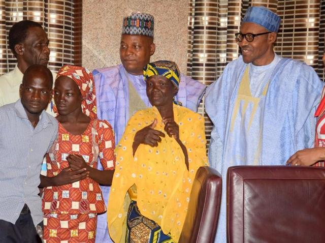 Amina Ali, the rescued Chibok schoolgirl (second left, front row), and her family members pose with Nigeria's President Muhammadu Buhari, right, and Borno state governor Kashim Shettima, centre, at the Presidential palace in Abuja, Nigeria.
