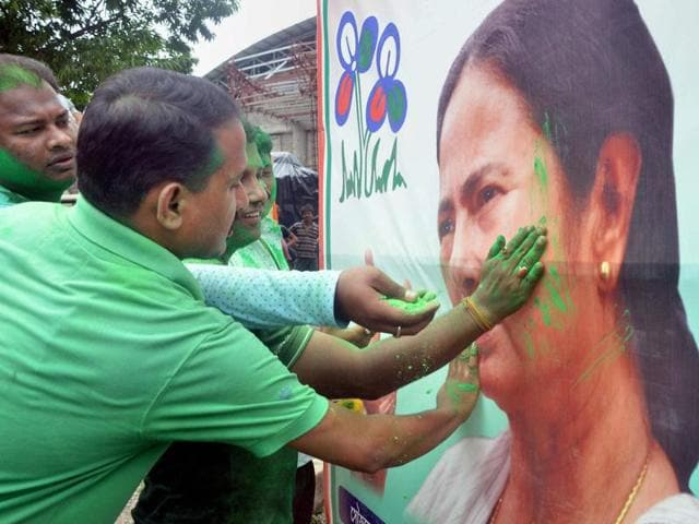 Trinamool Congress supporters smear colour on a poster of party chief Mamata Banerjee as they celebrate TMC's win in West Bengal assembly elections, in Tripura.