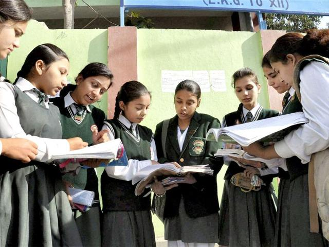 12th standard students give a last look to their notes as they prepare to appear in their CBSE exams at an examination centre in Moradabad .