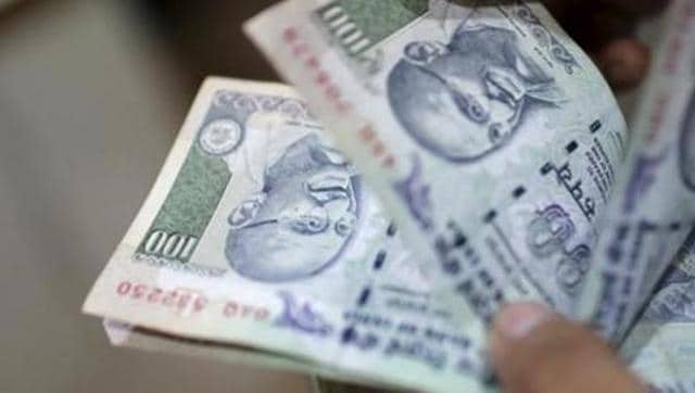 An employee counts Indian rupee currency notes in New Delhi.