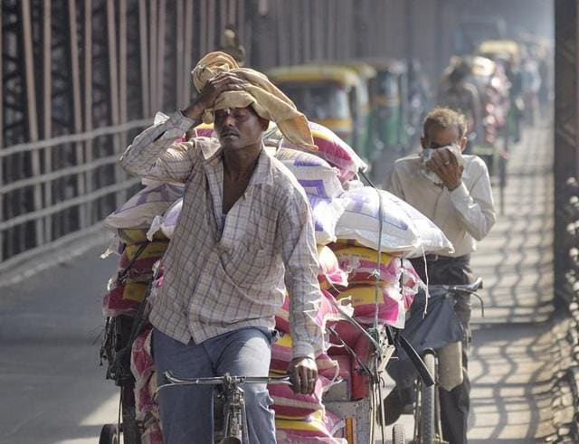 A man wipes sweat form his forehead as ferries goods in hot weather on his cycle rickshaw across the Old Yamuna bridge in New Delhi.