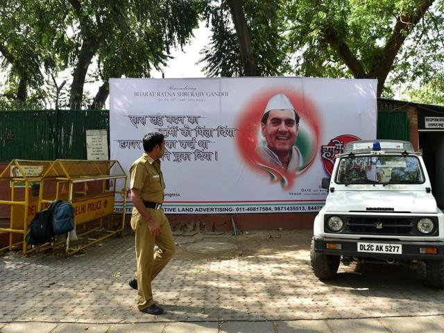 A police officer walks in front of a hoarding bearing the image of late Indian prime minister Rajiv Gandhi outside the All Indian Congress Committe office in New Delhi on May 19, 2016.