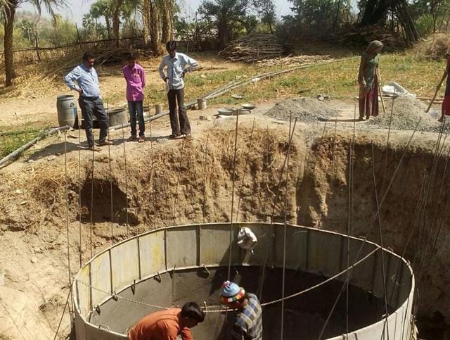 Health department staff work to complete construction of a well at Alirajpur district on Thursday.