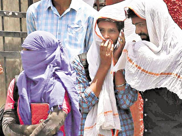 Students cover themselves with scarf and towel to beat the heat in Jaipur on Friday.