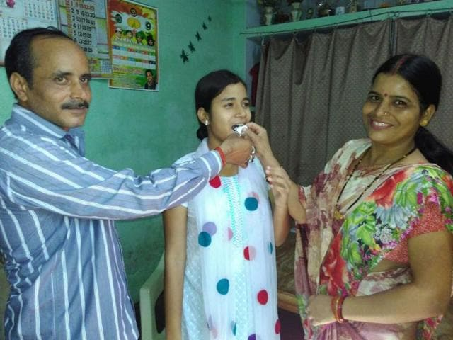 Saloni Maurya with her parents.  She topped Lucknow's St Anjani's Public School by scoring 97% in the science stream.