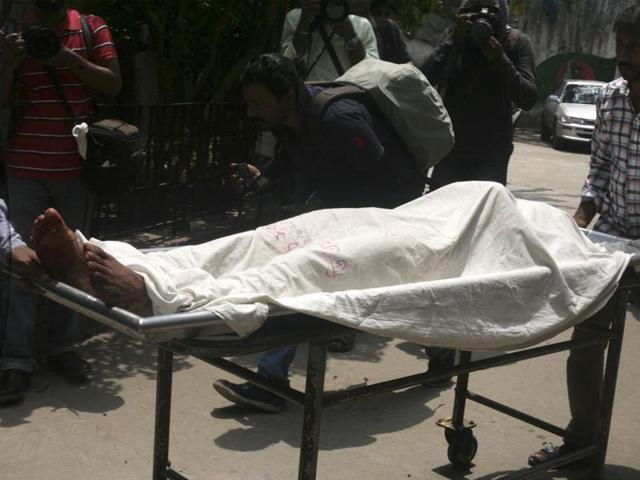 A Bangladeshi medical assistant pushes a trolley with the body of activist Xulhaz Mannan past media personnel at a hospital in Dhaka.