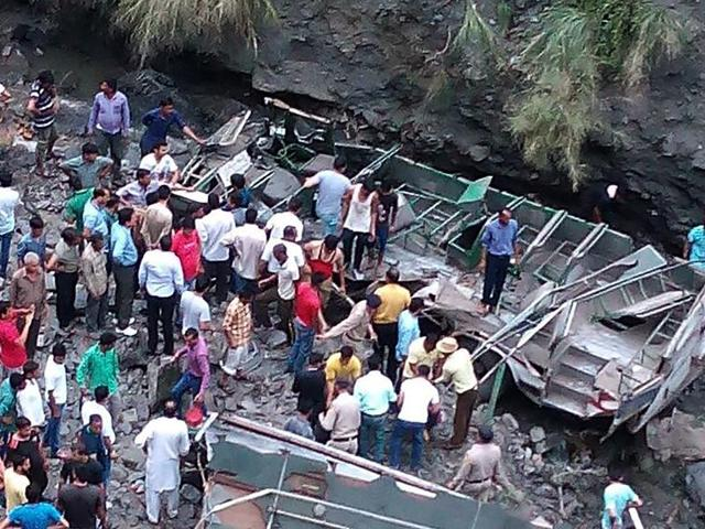 Bystanders gather beside the wreckage of a bus which fell into a gorge near Dalhousie in Chamba District of Himachal Pradesh.