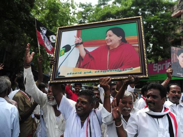 AIADMKmembers carry placards with the image of Jayalalithaa as they celebrate in front of her residence in Chennai.
