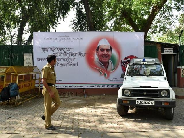 A police officer walks in front of a hoarding bearing the image of former prime minister Rajiv Gandhi outside the All India Congress Committee office in New Delhi.