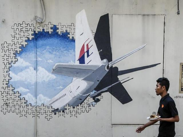 In this file photo, a man walks past a mural of flight MH370 in Shah Alam outside Kuala Lumpur, Malaysia.