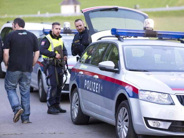 Police stand guard in Nenzing, near Vorarlberg, at the scene of a shooting where a man fatally shot two individuals and wounded eleven during a village party, before killing himself.