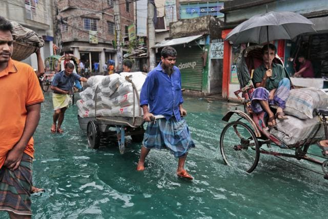 Bangladeshi men pull a loaded cart through a waterlogged street after heavy rainfall in Dhaka, Bangladesh.