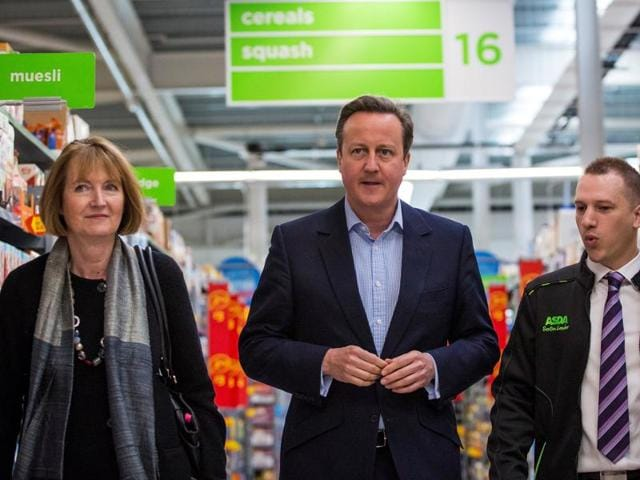 Britain's Prime Minister David Cameron (C) and former deputy Labour party leader Harriet Harman (L) speak to an Asda employee as they visit an Asda supermarket, to campaign ahead of the forthcoming EU referendum.
