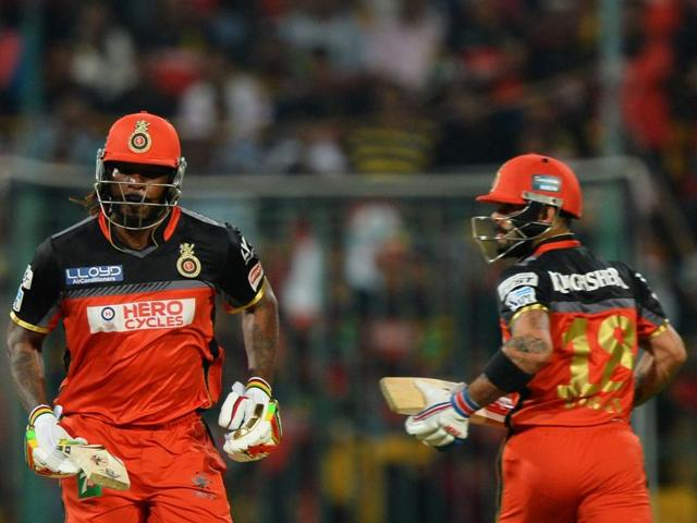 Royal Challengers Bangalore batsman Chris Gayle (L) and captain Virat Kohli run between the wickets during the IPL match against Kings XI Punjab, at The M. Chinnaswamy Stadium in Bangalore on May 18, 2016.