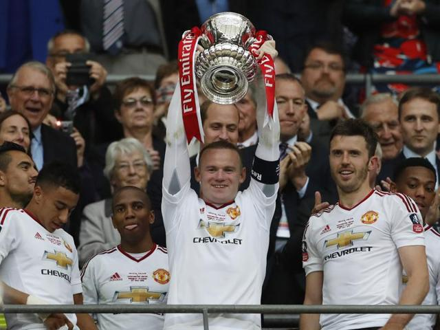 Manchester United's Wayne Rooney celebrates with the trophy after winning the FA Cup with teammates.