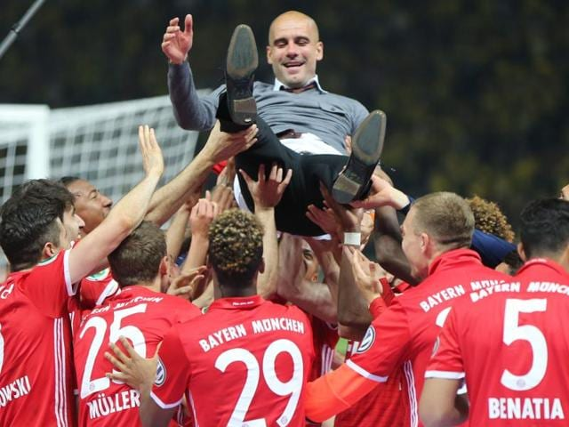 Pep Guardiola is thrown into the air by his players after winning the German Cup, DFB-Pokal final.