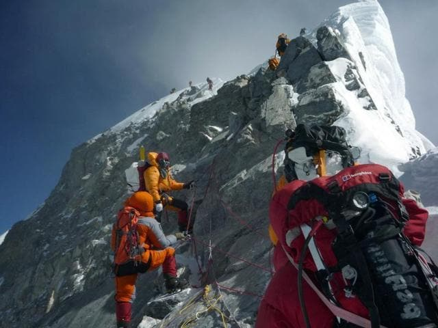 In this file photograph, unidentified mountaineers walk past the Hillary Step while pushing for the summit of Mount Everest as they climb the south face from Nepal.