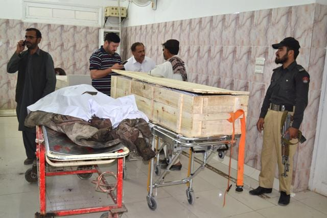 A Pakistani police officer and paramedics stand beside the bodies of the two men killed in a US drone strike in in Baluchistan province in Pakistan on May 22. A senior commander of the Afghan Taliban confirmed on Sunday that the extremist group's leader, Mullah Mohammad Akhtar Mansour, had been killed in the strike.