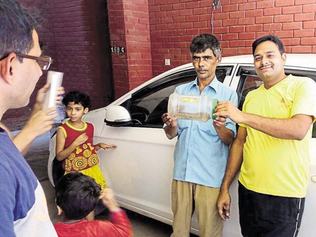 Salim Khan (in blue shirt) stands in front of the car from which the Russell's viper was rescued. The viper can be seen in the plastic container held by Khan and a local resident, Krishan Madan.